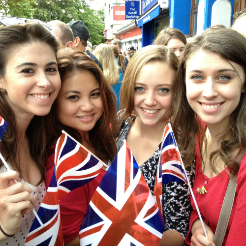 Four study abroad students in the United Kingdom holding UK flags