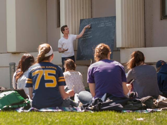 Graduate student teaching outside with chalkboard